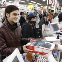 A foreign student buys a Nintendo Switch console in Osaka. | KYODO