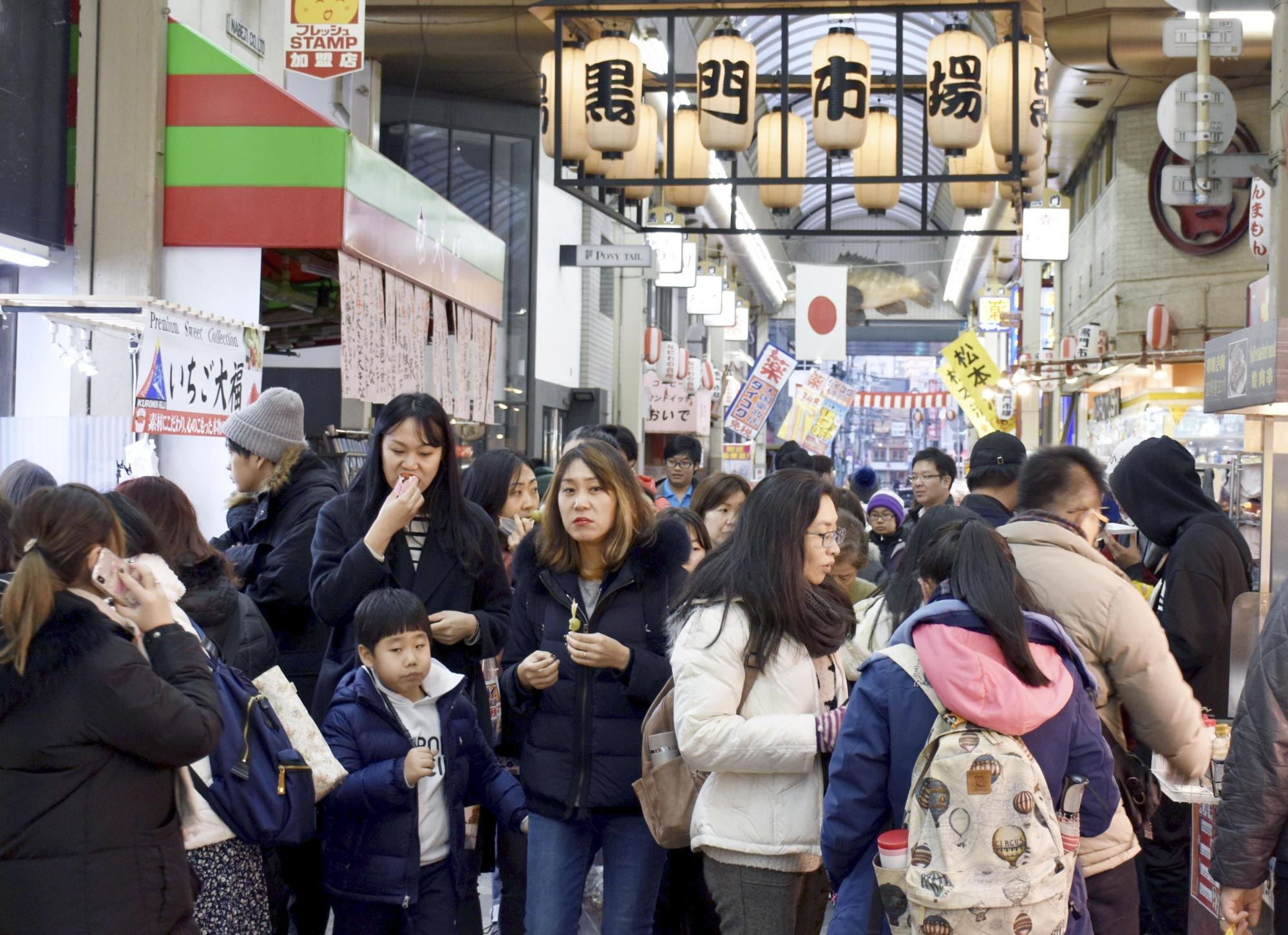 The Kuromon Ichiba shopping arcade, known as 'Osaka's kitchen' for its various food shops, is packed with foreign tourists on Jan. 20. | KYODO