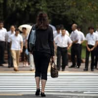 A woman waits to cross a road in the Kasumigaseki area of Tokyo. After years of pressure to give bigger pay raises — a key part of Prime Minister Shinzo Abe's campaign to restore stable economic growth — Japan Inc. is pushing back.   BLOOMBERG