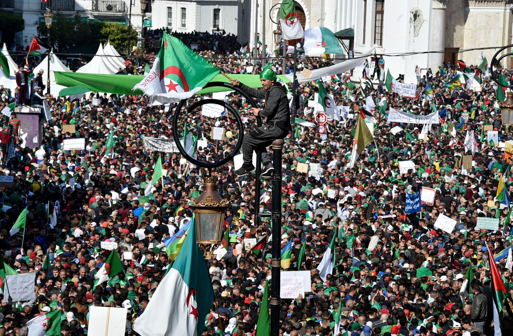 An Algerian protester atop a light pole waves a national flag  during a mass demonstration against ailing President Abdelaziz Bouteflika in Algiers on Friday. | AFP-JIJI
