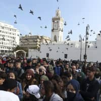 High school students march in central Algiers Sunday. The protesters are challenging President Abdelaziz Bouteflika's fitness to run for a fifth term in next month's election. | AP