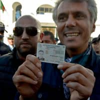Algerian businessman and political activist Rachid Nekkaz shows his ID card as he arrives at the constitutional council to submit his candidacy for the April 18 vote, in Algiers on Sunday. | AFP-JIJI