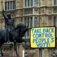 An anti-Brexit sign is seen next to a statue of King Richard I outside the Houses of Parliament in London on Monday. | REUTERS