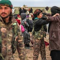 Civilians evacuated from the Islamic State (IS) group's embattled holdout of Baghouz wait at a screening area held by the U.S.-backed Kurdish-led Syrian Democratic Forces (SDF) in the eastern Syrian province of Deir Ezzor Wednesday. | AFP-JIJI