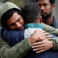 Relatives of a member of the Bangladeshi community wait for news on Sunday at a community center in Christchurch, New Zealand. | REUTERS