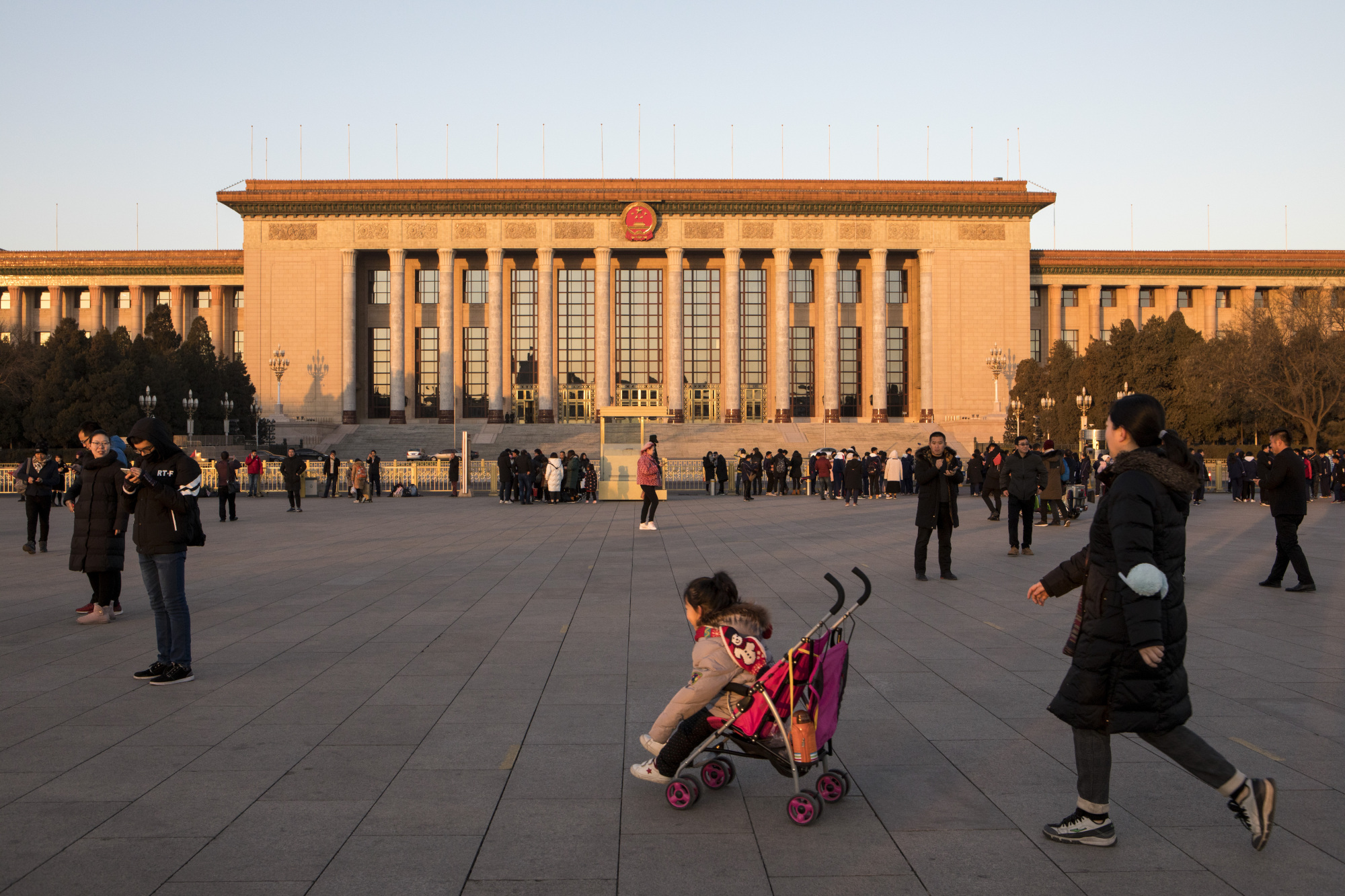 A young girl sits in a stroller in front off the Great Hall of the People at Tiananmen Square in Beijing in January. | BLOOMBERG