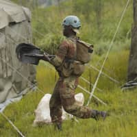 A soldier carries shovels during a rescue operation in Chimanimani about 600 km south east of Harare Tuesday. According to the government Cyclone Idai has killed more than 100 people in Chipinge and Chimanimani and according to residents the figures could be higher because the hardest-hit areas are still inaccessible.   AP
