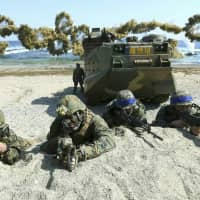 Marines of the U.S. (left) and South Korea, wearing blue headbands on their helmets, take positions after landing on a beach during the joint military combined amphibious exercise, called Ssangyong, part of the Key Resolve and Foal Eagle military exercises, in Pohang, South Korea, in 2016. South Korea and the U.S. say they've decided to end their springtime military drills to back diplomacy with North Korea. | KIM JUN-BUM / YONHAP / VIA AP