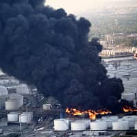 A plume of smoke rises from a petrochemical fire at the Intercontinental Terminals Company Monday in Deer Park, Texas. The large fire at the Houston-area petrochemicals terminal will likely burn for another two days, authorities said, noting air quality around the facility was testing within normal guidelines. | AP