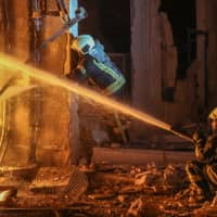 Members of the Syrian Civil Defense (The White Helmets) put out a fire at the site of reported airstrikes inside the jihadi-held city of Idlib Wednesday. | AFP-JIJI