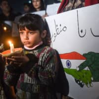 A Pakistani girl holds a candle during a vigil for peace in Lahore on Monday. Tensions have soared between India and Pakistan since a suicide bombing in Kashmir last month, claimed by Pakistan-based militants, killed 40 Indian paramilitary police. | AFP-JIJI
