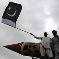 A Pakistani supporter of the Jamaat-e-Islami party holds a Pakistan national flag beside a replica of a missile during an anti-Indian protest rally in Karachi on Thursday. | AFP-JIJI