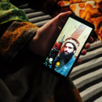 A sister of suspected militant Owais Malik shows a picture of him on her phone at her home in Kashmir's Kulgam district on Feb. 16. | REUTERS