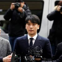 Seungri, a member of South Korean K-pop band Big Bang, arrives to be questioned over a sex bribery case at the Seoul Metropolitan Police Agency in Seoul Thursday.