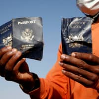 A man holds passengers' passports found at the scene of the Ethiopian Airlines Flight ET 302 plane crash, near the town of Bishoftu, near Addis Ababa, Tuesday. | REUTERS