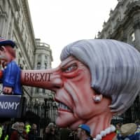 An effigy of Prime Minister Theresa May is carried past the entrance of Downing Street, where the British prime minister's official residence and office is located, during a 'Peoples Vote' anti-Brexit march in London on Saturday. | AP