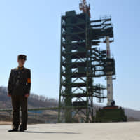 Two North Korean soldiers stand guard in front of an Unha-3 rocket at the Sohae Satellite Launch Station in Tongchang-Ri, North Korea, in April 2012. | AFP-JIJI