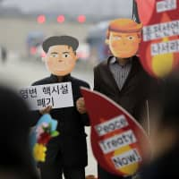 Protesters wearing masks of U.S. President Donald Trump and North Korean leader Kim Jong Un stand during a rally demanding the denuclearization of the Korean Peninsula and a peace treaty, near the U.S. Embassy in Seoul last Thursday. | AP