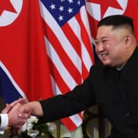 U.S. President Donald Trump speaks with North Korean leader Kim Jong Un during a meeting at the Metropole Hotel in Hanoi on Feb. 27. | AFP-JIJI