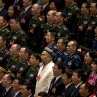 A delegate in traditional Uighur dress stands with military delegates as they sing the Chinese national anthem during the closing session of China's National People's Congress at the Great Hall of the People in Beijing on Friday. | AP