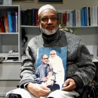 Al Noor mosque shooting survivor Farhid Ahmed poses with a photo of his wife, Husna, who was killed in the attack, after an interview with Reuters in Christchurch, New Zealand, Monday. | REUTERS