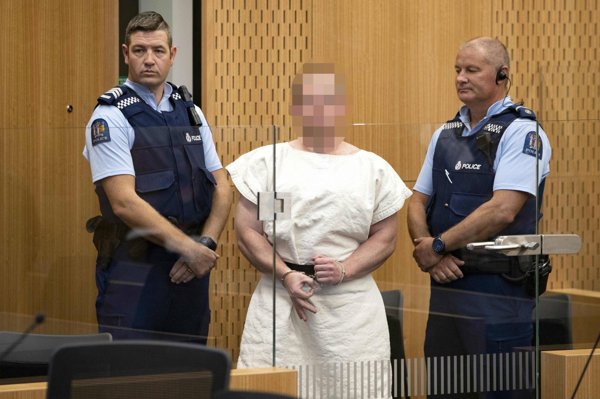 Australian Brenton Tarrant, charged in relation to the massacre at two mosques in Christchurch, makes a sign to the camera during his appearance in the Christchurch District Court on Saturday. | AFP-JIJI