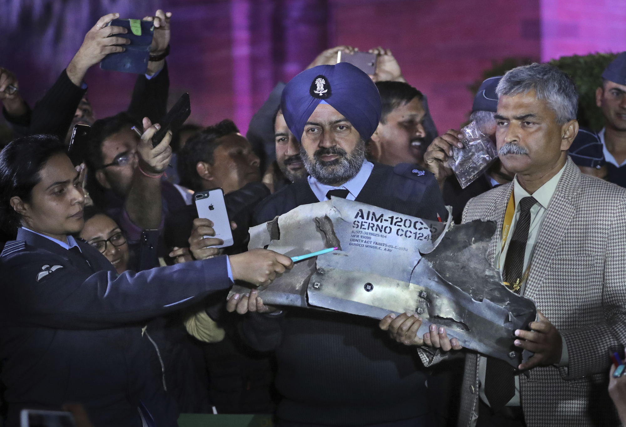 Indian defense officials in New Delhi on Thursday display part of an air-to-air missile that allegedly was fired by a Pakistani Air Force aircraft that violated Indian airspace. | AP