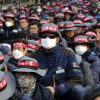 People wearing masks to guard against air pollution attend a rally in Seoul on March 6. | AP