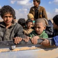 Children believed to be from the Yazidi community, who had been captured by Islamic State group fighters, are pictured after being evacuated from the group's embattled holdout of Baghouz, Syria, on March 6. | AFP-JIJI