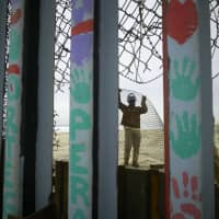 A construction worker replaces fencing lining the north side of the border wall separating San Diego, California, from Tijuana, Mexico, Monday. | AP