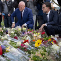 Dutch Prime Minister Mark Rutte (right) and Justice Minister Ferd Grapperhaus lay flowers at a makeshift memorial for victims of a Monday shooting incident in a tram in Utrecht on Tuesday. | AP
