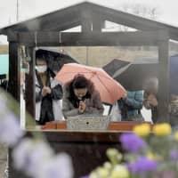 People pray Monday at the now-closed Okawa Elementary School in Ishinomaki, Miyagi Prefecture, where more than 80 pupils and teachers were killed in a massive tsunami on March 11, 2011. | KYODO