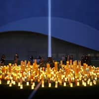 Candles light the field at the J-Village national soccer training center in Fukushima Prefecture on Sunday night to mourn the victims of the March 2011 disasters and pray for reconstruction of the area. | KYODO