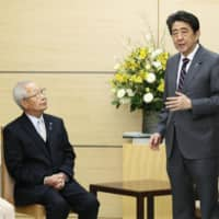 Prime Minister Shinzo Abe meets with a group representing the families of people abducted by North Korea, at his office in Tokyo on Wednesday. The visitors included Sakie Yokota (left) and Shigeo Iizuka. | KYODO