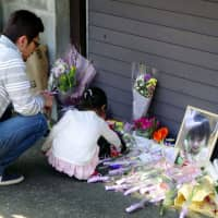 People lay flowers in front of an apartment building in Tokyo's Meguro Ward on March 2 to mark the one-year anniversary of the death of 5-year-old Yua Funato after alleged abuse by her parents. A record 1,394 children were the victims of child abuse in 2018, according to the National Police Agency's report released Thursday. | KYODO