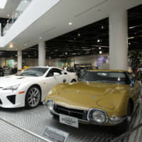 A Toyota 2000GT coupe (right) is displayed in a Yamaha Motor Co. showroom in Iwata, Shizuoka Prefecture, in February 2015. | BLOOMBERG