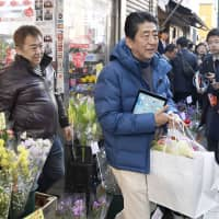 Prime Minister Shinzo Abe leaves a store in Tokyo's Shinagawa Ward in February after using a cashless payment system. | KYODO