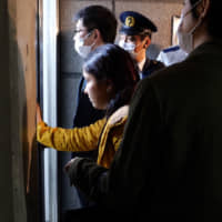 Yasemin Colak, the wife of Kurdish detainee Mehmet Colak, tries to see what's happening inside the Tokyo Regional Immigration Bureau in Minato Ward after an ambulance crew entered the building to check on her husband's condition on the evening of March 12. | CHISATO TANAKA