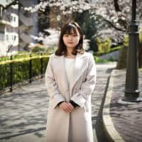 Marina Fukumoto poses in Tokyo on Wednesday. Fukumoto, a 22-year-old martial arts enthusiast who this year graduated with a law degree from elite Keio University in Tokyo, is about to start her professional career. | BLOOMBERG