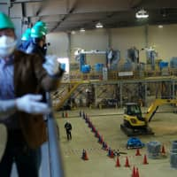 Reporters visit the site where soil contaminated by radiation from the three core meltdowns at the Fukushima No. 1 power plant is sorted and distributed to a storage facility, on Feb. 7. | RYUSEI TAKAHASHI