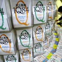 A shopper looks at a copy of author Haruki Murakami's book titled '1Q84' at a bookstore in Tokyo in May 2009. | ASSOCIATED PRESS