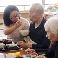 A Taiwanese caregiver (left) helps an elderly man eat a meal at a nursing facility in Asahikawa, Hokkaido, in 2018. | KYODO