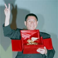 Kitano reacts after winning the Golden Lion for his film 'Hana-Bi' at the Venice Film Festival on Sept. 6, 1997. | AP / VIA KYODO