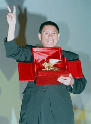 Kitano reacts after winning the Golden Lion for his film
