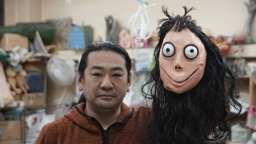 Artist Keisuke Aiso, creator of the goggle-eyed creature that was later dubbed Momo, holds up an unauthorized replica mask of the monster that a friend brought back as a souvenir from Mexico's Day of the Dead festivities, at his two-story studio on the outskirts of Tokyo on Monday. | RYUSEI TAKAHASHI