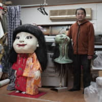 Artist Keisuke Aiso stands next to some of his other creations at his studio on the outskirts of Tokyo. | RYUSEI TAKAHASHI