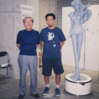 Takashi Murakami in 1998 with Osamu Miyawaki, founder of the figurine company Kaiyodo, alongside a prototype for Murakami's Miss ko2. | COURTESY TAKASHI MURAKAMI/KAIKAI KIKI CO., LTD