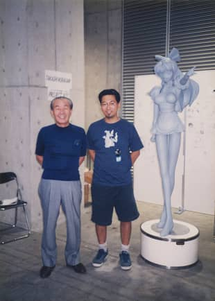 Takashi Murakami in 1998 with Osamu Miyawaki, founder of the figurine company Kaiyodo, alongside a prototype for Murakami