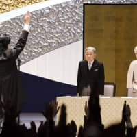 Prime Minister Shinzo Abe performs a traditional banzai cheer for Emperor Akihito and Empress Michiko at a ceremony marking the 30th year of his reign at the National Theatre in Tokyo on Feb. 24. | AP
