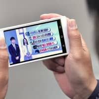 A man watches an NHK program on his cellphone. The top court says owners of cellphones with television functions must pay subscription fees to the public broadcaster. | KYODO